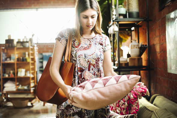 Young woman standing in a shop, holding a cushion. - Stock Photo - Images