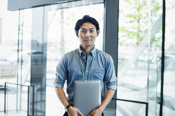 Businessman wearing blue shirt standing indoors by glass wall, holding laptop, looking at camera. - Stock Photo - Images