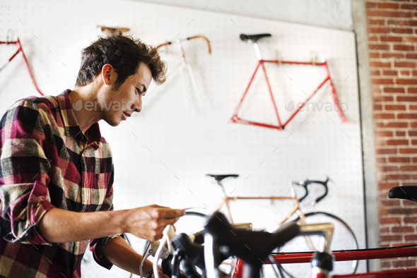 A man in a cycle shop, reading the price label on a bike. - Stock Photo - Images
