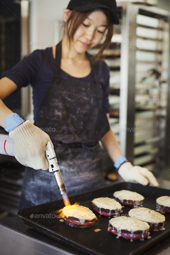 Woman working in a bakery, wearing oven gloves, using blowtorch, melting cheese on sandwiches. - Stock Photo - Images