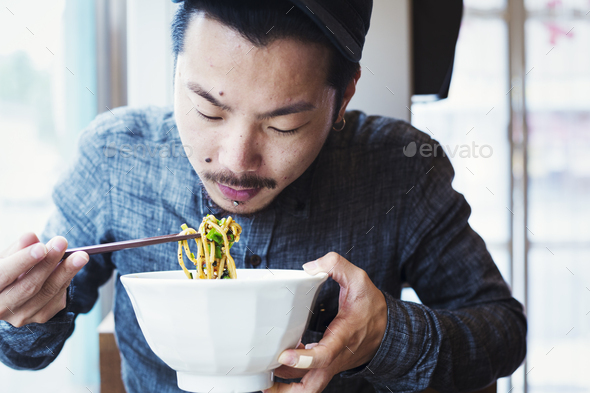 A ramen noodle cafe in a city.  A man seated eating ramen noodles from a large broth bowl. - Stock Photo - Images