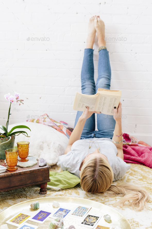 A young woman in jeans lyng on her back with her legs against the wall. - Stock Photo - Images