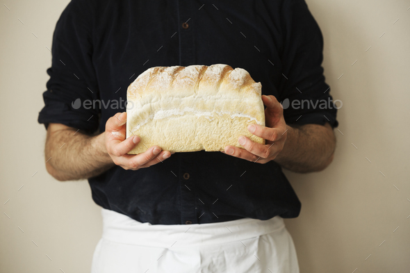 Close up of a baker holding a freshly baked loaf of white bread. - Stock Photo - Images