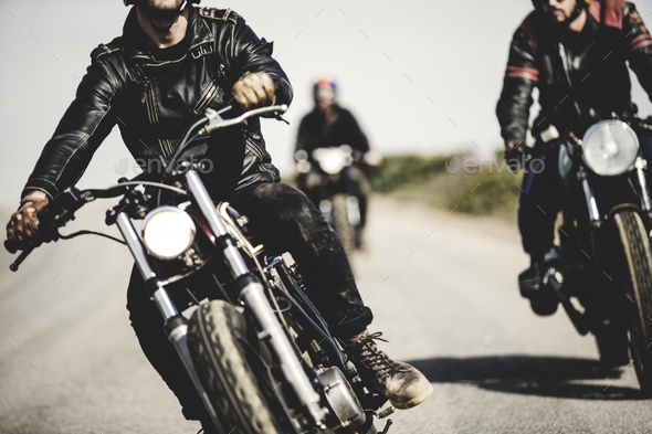Three men wearing leather jackets riding cafe racer motorcycles along rural road. - Stock Photo - Images