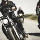 Three men wearing leather jackets riding cafe racer motorcycles along rural road. - PhotoDune Item for Sale