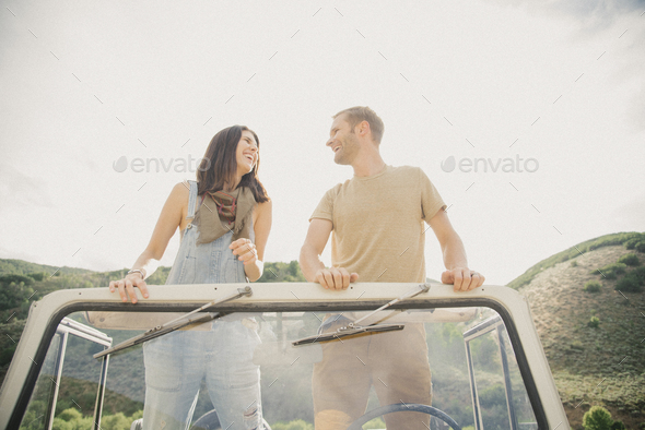 A couple on a road trip in the mountains standing side by side in a jeep looking around. - Stock Photo - Images