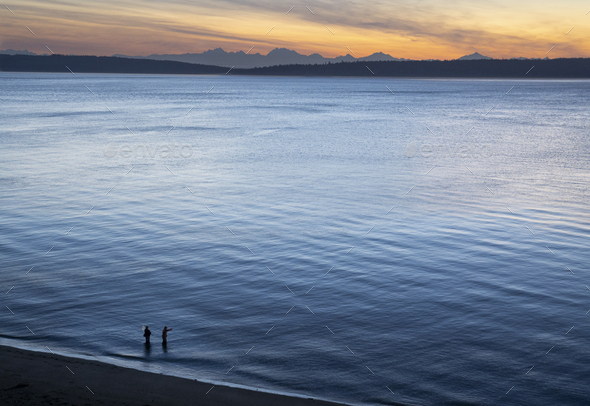 A view from above of a guide and a fly fisherman at the water's edge, fishing for salmon and sea run - Stock Photo - Images