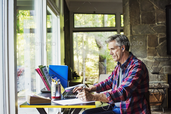 A man seated at a desk at home, working on a laptop computer. - Stock Photo - Images