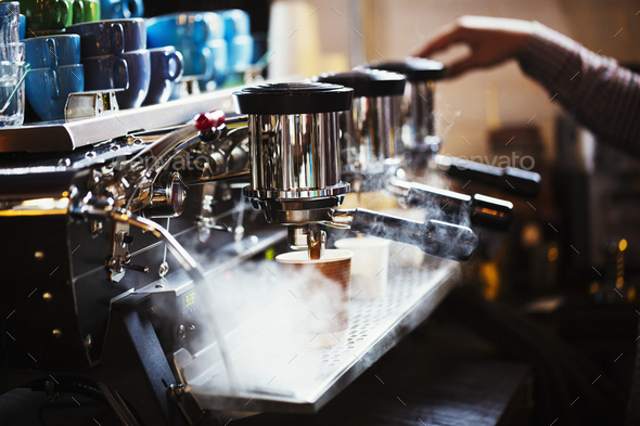 Specialist coffee shop. A person working at a large coffee machine, with three perculating - Stock Photo - Images
