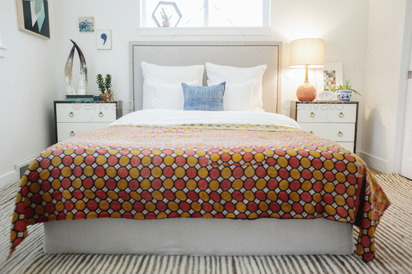 A bedroom in an apartment with a double bed and beside cabinets, and a vivid retro style patterned - Stock Photo - Images
