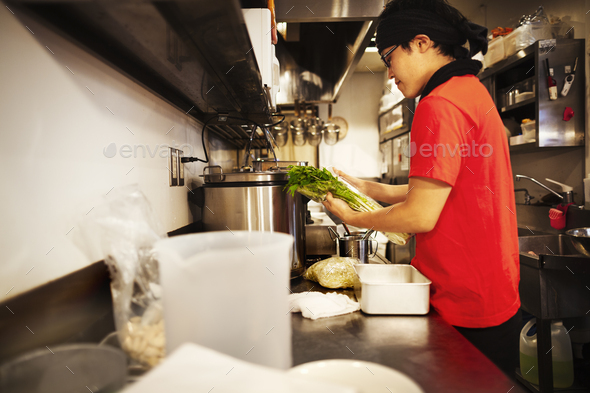 The ramen noodle shop. A chef working in a kitchen preparing food using a stove and large pans. - Stock Photo - Images
