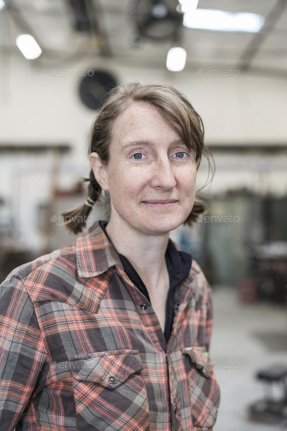 Blond woman wearing checkered shirt standing in metal workshop, smiling at camera. - Stock Photo - Images