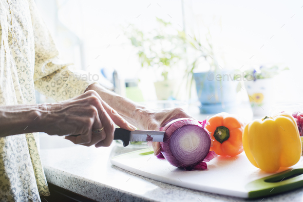 A woman standing in a kitchen, cutting a red onion and peppers on a chopping board. - Stock Photo - Images