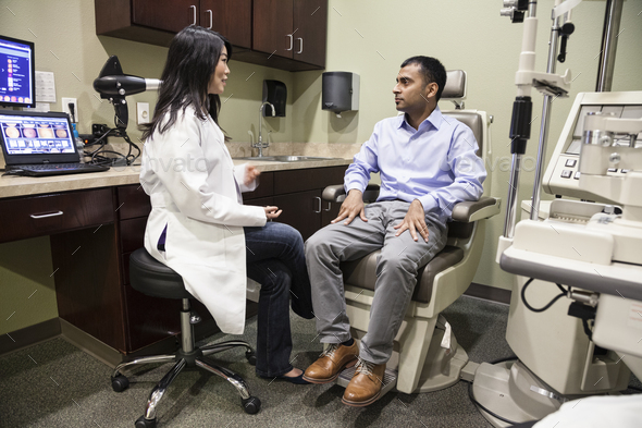 Asian woman ophthalmologist working with an east Indian male patient in an examination office. - Stock Photo - Images