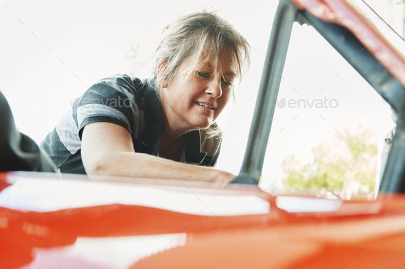 Mature woman repairing a car, looking under bonnet. - Stock Photo - Images