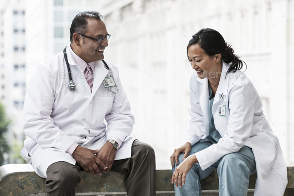 HIspanic man and asian woman doctors conferring over a case in a hospital. - Stock Photo - Images