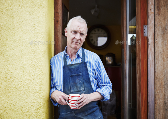 A craftsman standing in a doorway holding a mug. - Stock Photo - Images