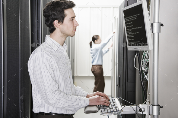 A male computer technician standing in an aisle of racks of servers in a computer server farm - Stock Photo - Images