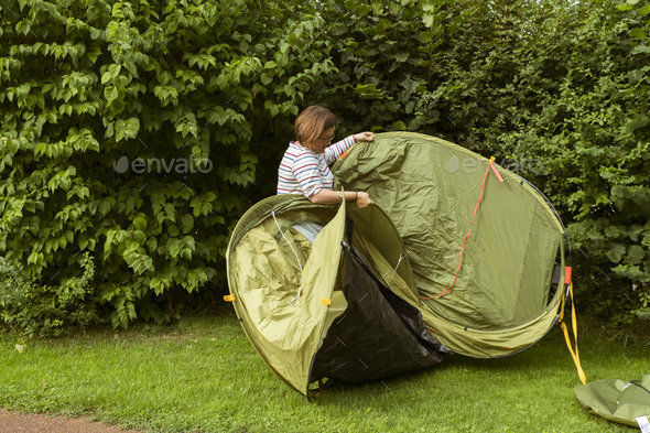 A woman putting up a green pop up tent in a sheltered spot by a tall hedge. - Stock Photo - Images