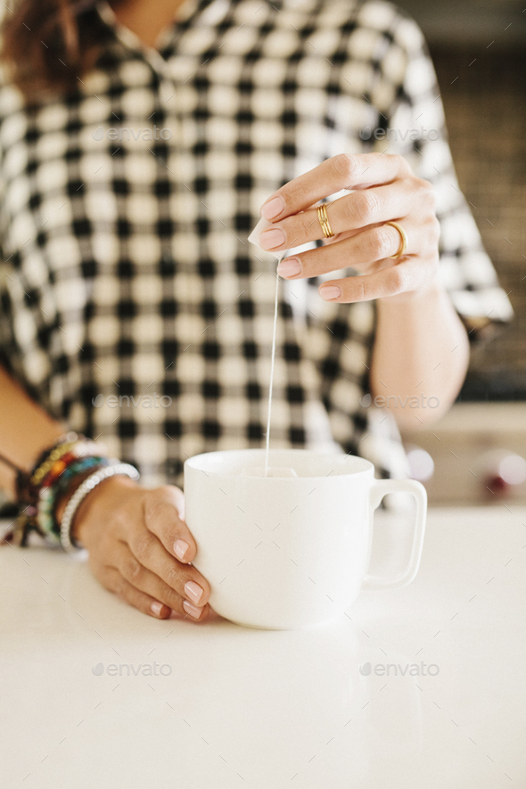 Woman wearing a chequered shirt making a cup of tea. - Stock Photo - Images
