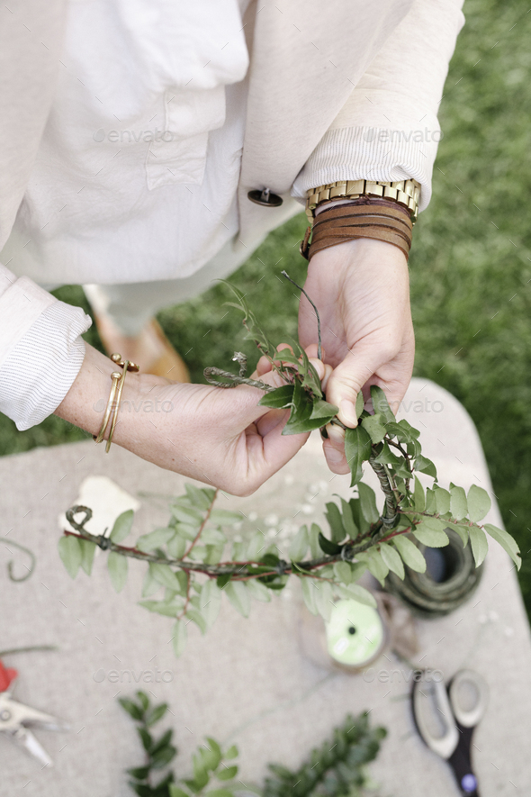 Close up of a woman, standing in a garden, making a flower wreath. - Stock Photo - Images
