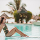 Woman relaxing by the pool in a luxury hotel resort enjoying perfect beach holiday vacation - PhotoDune Item for Sale