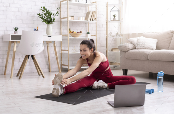 Yoga instructor running online training session via laptop at home - Stock Photo - Images