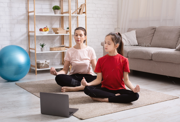 Home yoga workout. Mom and teen daughter meditating to online tutorial on laptop in living room - Stock Photo - Images