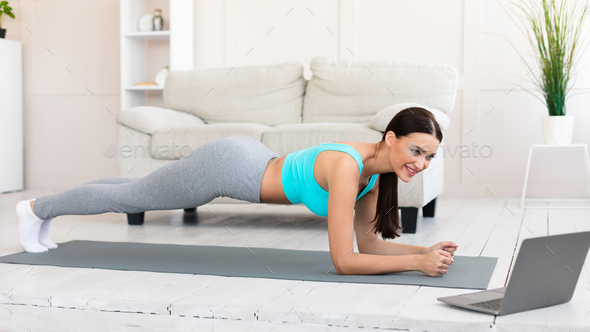 Young Woman At Laptop Exercising Doing Plank During Home Workout - Stock Photo - Images