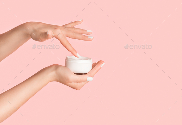 Unrecognizable girl applying cream from jar onto her hands against pink background, blank space - Stock Photo - Images