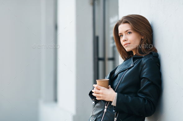 Happy casual brunette female staying near grey wall with coffee - Stock Photo - Images