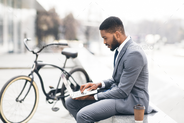 Handsome guy working on laptop sitting on parapet - Stock Photo - Images