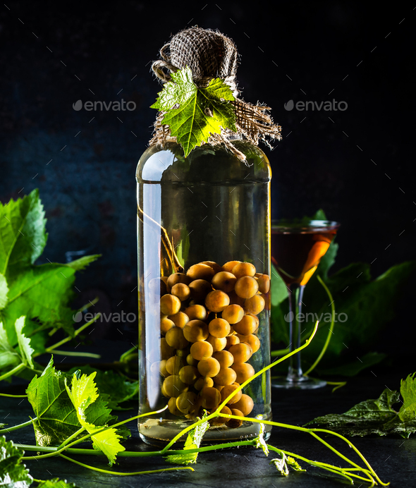 Chilean brandy aguardiente with whole bunch of grapes inside bottle - Stock Photo - Images