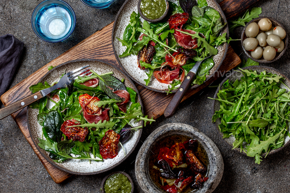 Fresh salad with green spinach, rucola, ham serrano dried tomatoes, top view - Stock Photo - Images