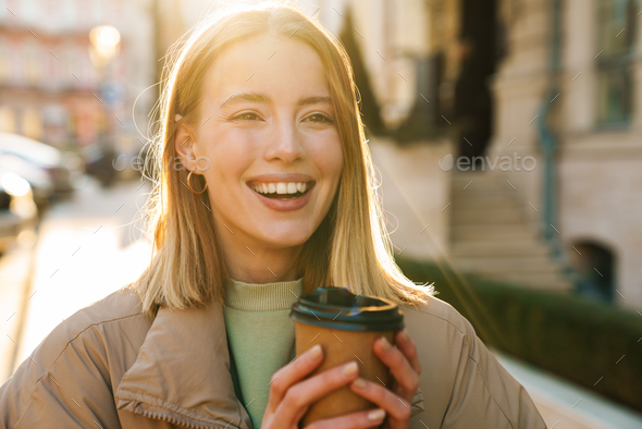Portrait of joyful woman drinking coffee while walking at city street - Stock Photo - Images