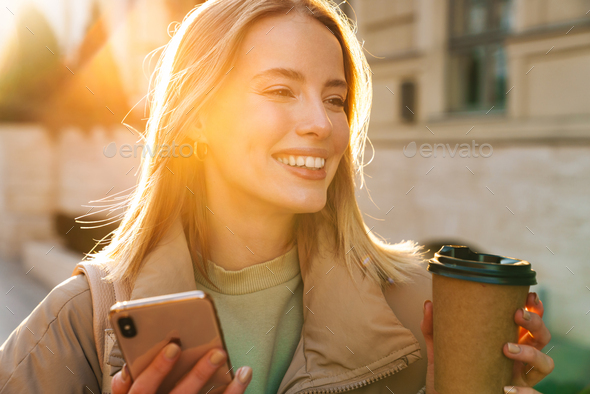 Portrait of woman using cellphone and drinking coffee while walking - Stock Photo - Images