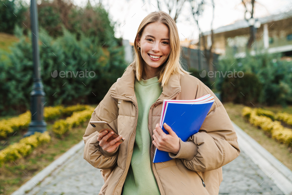 Portrait of smiling woman using mobile phone while walking in park - Stock Photo - Images