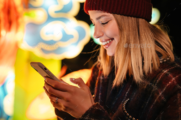 Photo of woman smiling and typing on mobile phone while walking - Stock Photo - Images