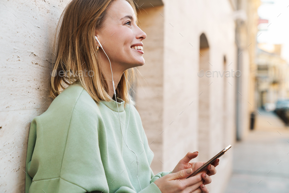 Portrait of smiling young woman using earphones and mobile phone - Stock Photo - Images