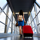 Young girl traveler walking with carrying hold suitcase in the airport. - PhotoDune Item for Sale