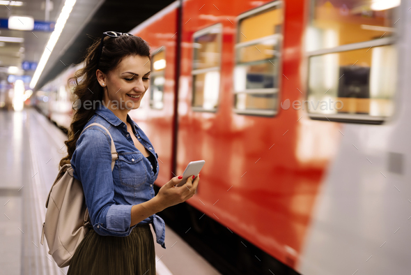 Beautiful woman using her cell phone on subway platform. - Stock Photo - Images