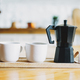 Two white ceramic mugs and geyser coffee maker on wooden tray on kitchen table - PhotoDune Item for Sale