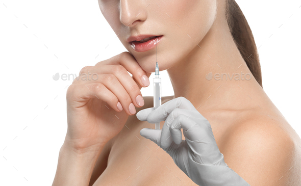 Plastic surgery beauty concept - beautiful young woman face hand in glove syringe making injection - Stock Photo - Images