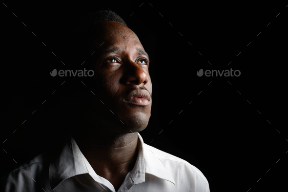 Young African businessman in the dark against black background - Stock Photo - Images