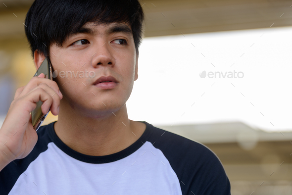 Young handsome Asian tourist man at the railway station - Stock Photo - Images