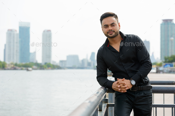 Young handsome bearded Indian businessman in the city - Stock Photo - Images
