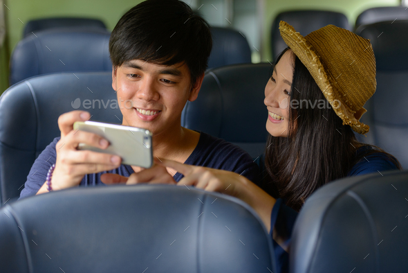 Young Asian tourist couple travelling together at the railway station - Stock Photo - Images