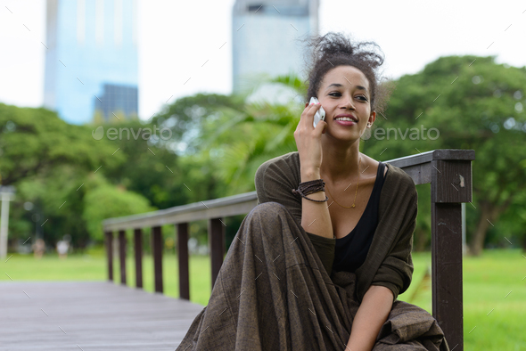 Portrait of young beautiful African woman at the park outdoors - Stock Photo - Images