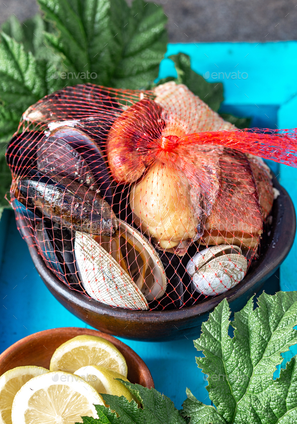 Curanto Kuranto. Different seafood and meat cooked in a pit on the coals under the ground - Stock Photo - Images