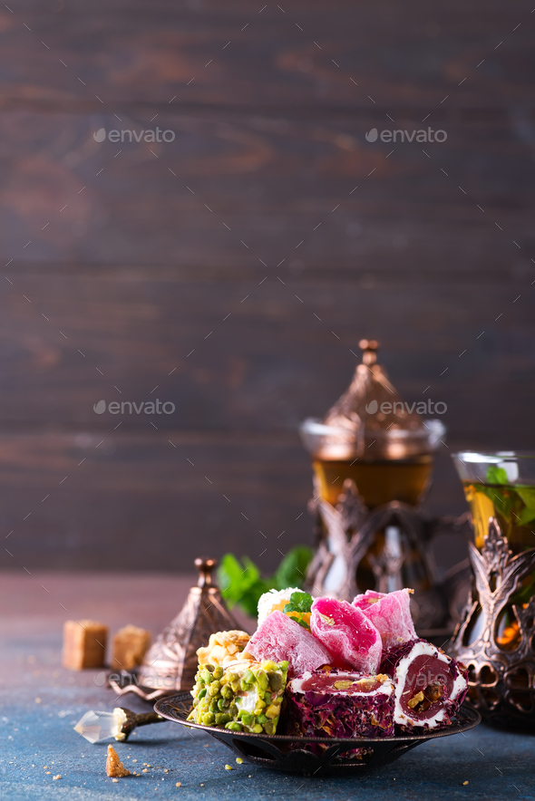 Bowl with various pieces of turkish delight lokum and black tea with mint on a dark background - Stock Photo - Images